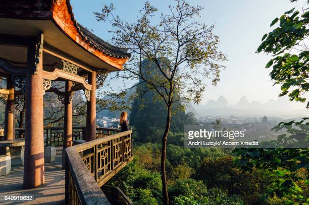 Young woman enjoys view over Yangshuo, karst mountains