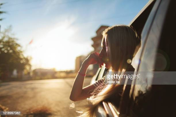 young woman enjyoing looking out of the window of a car - one young woman only stock pictures, royalty-free photos & images