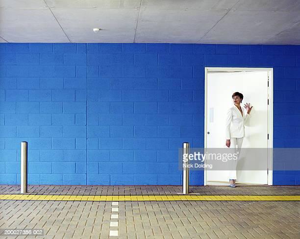 Young woman entering car park through white door
