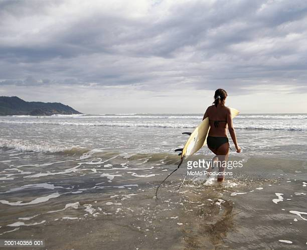 Young woman entering ocean, carrying surfboard, sunset, rear view