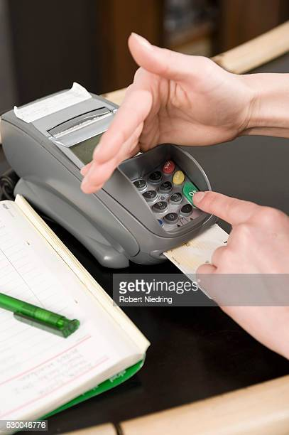young woman entering pin in credit card reader - pin stock pictures, royalty-free photos & images