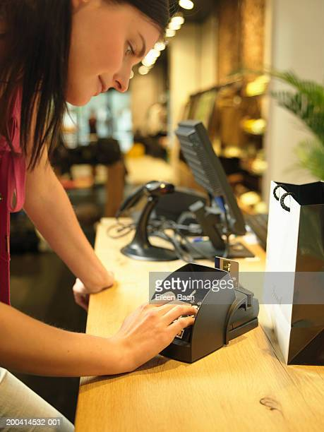Young woman entering pin number into machine at counter, smiling