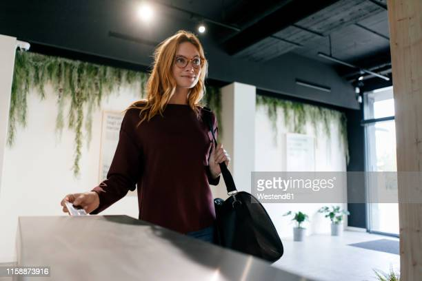 young woman entering spa area with chip card - スポーツバッグ ストックフォトと画像