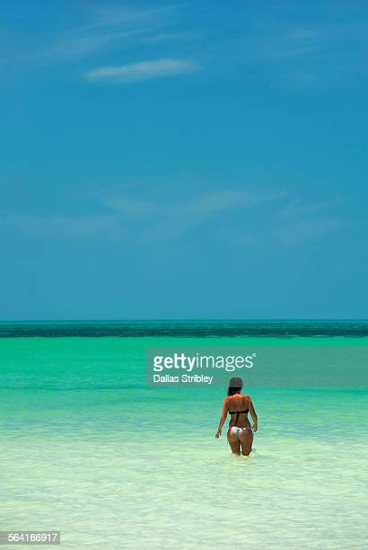 Young woman entering the blue-green sea at Holbox