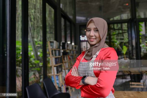 young woman entrepreneur in front of cafe - islam stock pictures, royalty-free photos & images