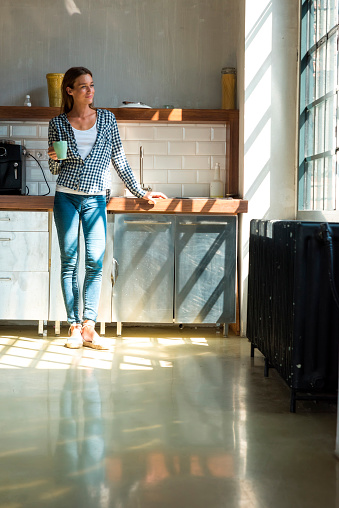 Young woman entrepreneur standing in company kitchen, drinking coffee - gettyimageskorea