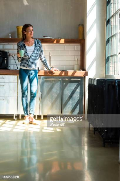 Young woman entrepreneur standing in company kitchen, drinking coffee