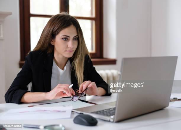 young woman entrepreneur working at desk in office - vestuário de trabalho formal imagens e fotografias de stock