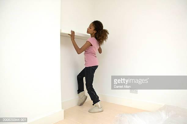Young woman erecting shelf, side view