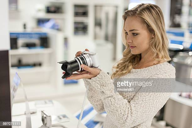 Young woman examining a camera in a shop