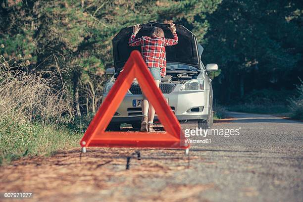 Young woman examining damaged car with a warning triangle in the road