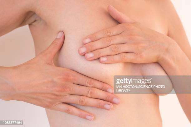 young woman examining her breast - mani su seno foto e immagini stock