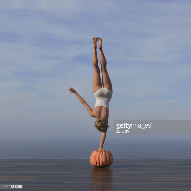 young woman excercising handstand on pumpkin - miglioramento digitale foto e immagini stock