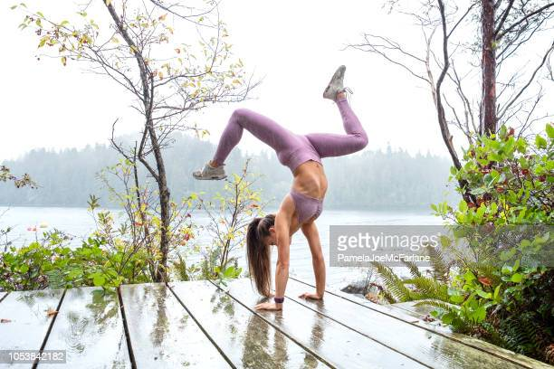 young woman executing split handstand in rain on outdoor deck - purple pants stock pictures, royalty-free photos & images