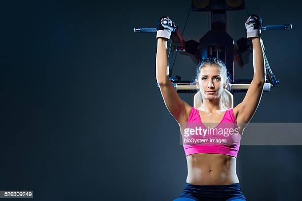肩に若い女性運動マシンを - エクササイズ用具 ストックフォトと画像