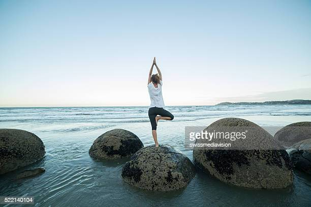 Young woman exercises yoga on a boulder at Moeraki boulders