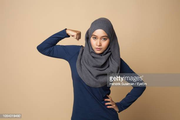 young woman exercising against beige background - beige background stock pictures, royalty-free photos & images