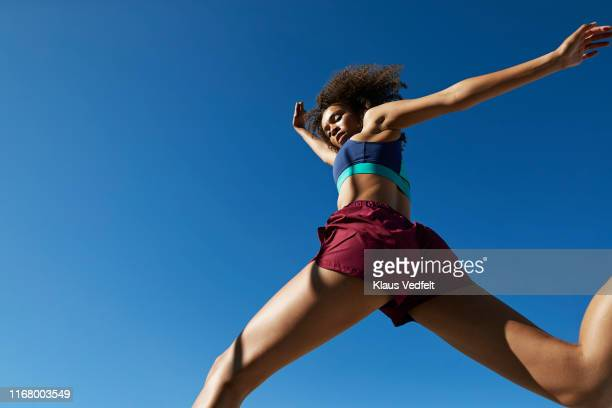 young woman exercising against clear sky - legs apart stock pictures, royalty-free photos & images