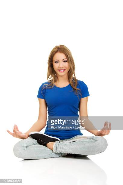 young woman exercising against white background - cross legged stock pictures, royalty-free photos & images