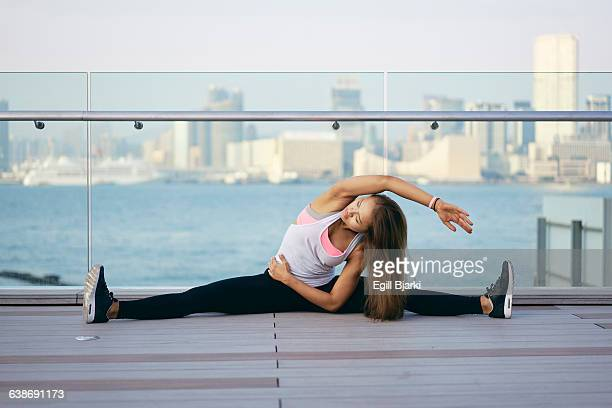 Young woman exercising and doing the splits on waterfront, Hong Kong