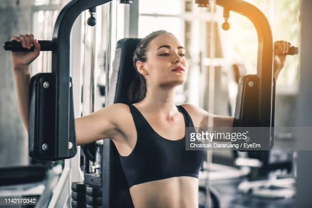 young woman exercising at gym - ブラトップ ストックフォトと画像