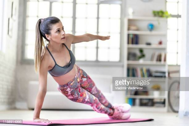 young woman exercising at home, side plank pose - allenamento foto e immagini stock