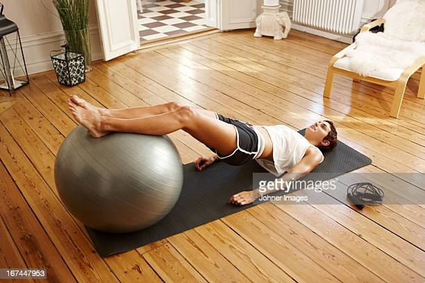 young woman exercising at home with fitness ball - fitness ball stock pictures, royalty-free photos & images