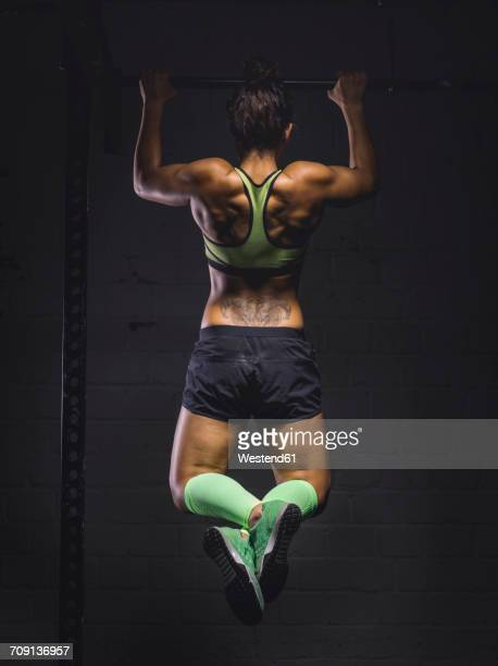 young woman exercising at power rack - chin ups stock photos and pictures