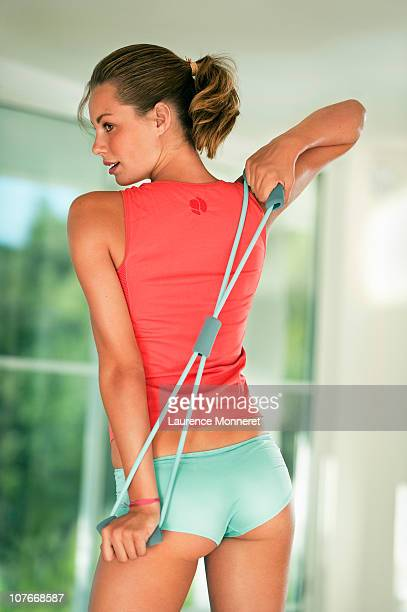 Young woman exercising back with elastic