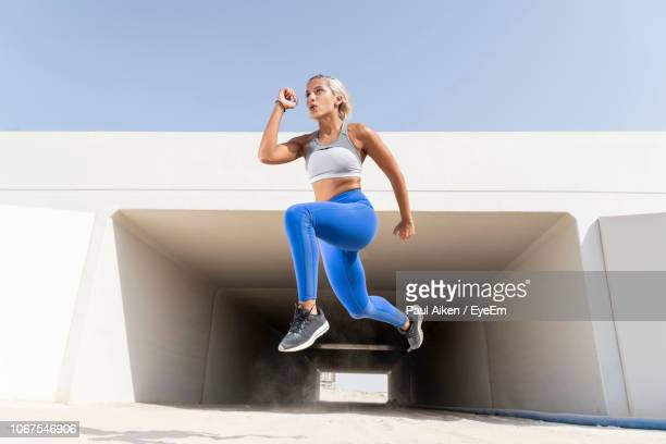 young woman exercising by built structure against sky - aikāne stock pictures, royalty-free photos & images