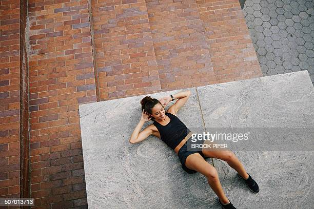 Young woman exercising core doing crunches