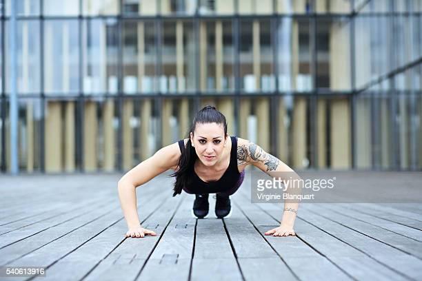 Young woman exercising, doing push-ups in Paris