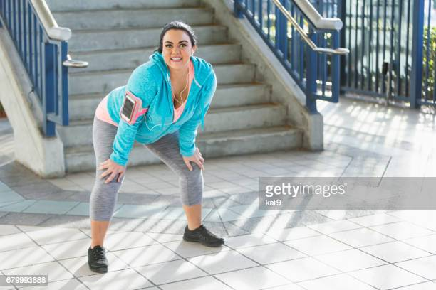 young woman exercising in city, stretching - plus size model stock pictures, royalty-free photos & images