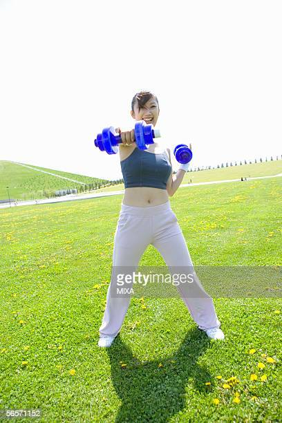 Young woman exercising in field with dumbbells