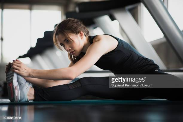 young woman exercising in gym - 足を開く ストックフォトと画像