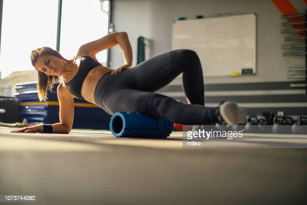 young woman exercising in gym - de rola imagens e fotografias de stock
