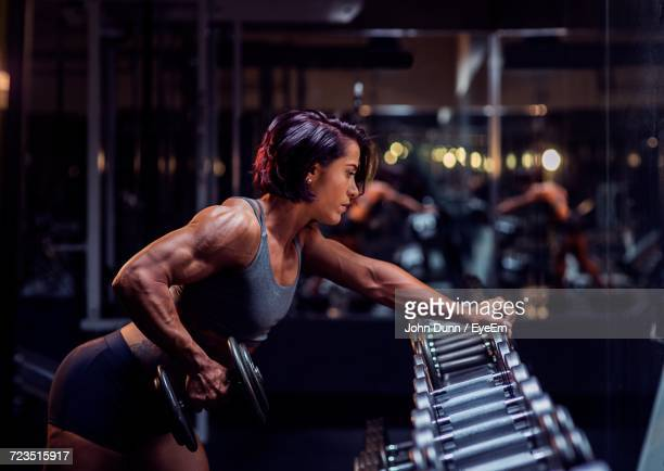 young woman exercising in gym - bodybuilding stock-fotos und bilder