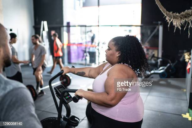 young woman exercising in the gym - effort stock pictures, royalty-free photos & images