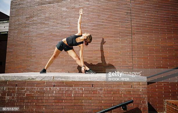 young woman exercising in urban area doing yoga - aufwärmen stock-fotos und bilder