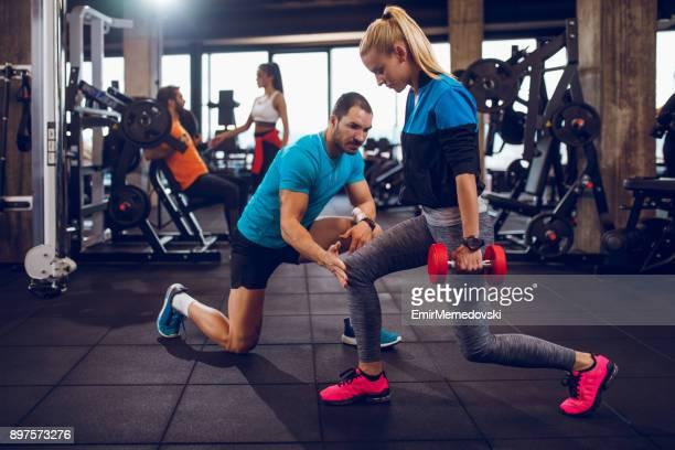 jovem mulher exercitando lunges com halteres na academia - flexionando perna - fotografias e filmes do acervo