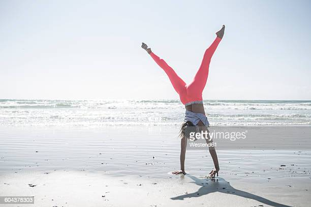 Young woman exercising on beach doing a handstand
