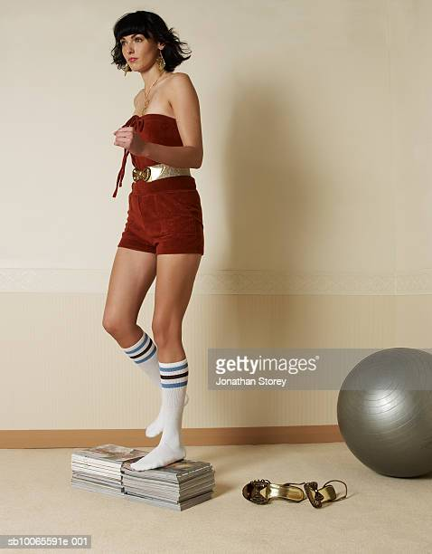 Young woman exercising on books