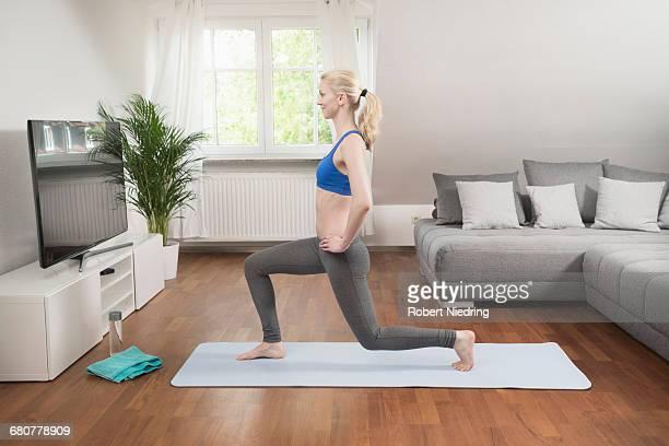young woman exercising on exercise mat in living room, bavaria, germany - flexionando perna - fotografias e filmes do acervo