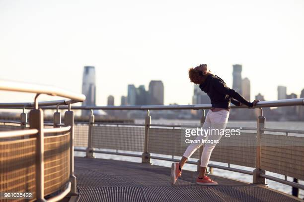 young woman exercising on footpath by river in city against clear sky - bending over backwards stock photos and pictures
