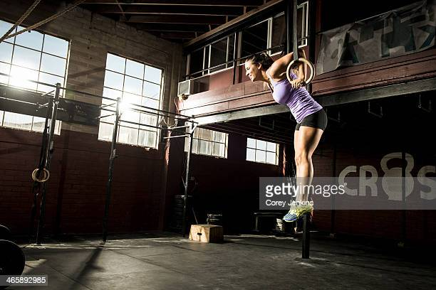 Young woman exercising on gymnastic ring