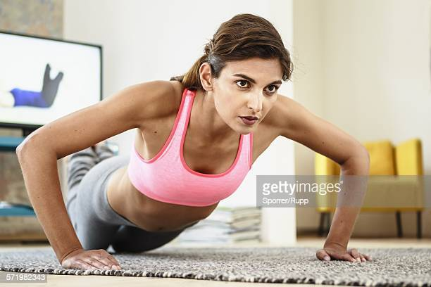 Young woman exercising on living room floor in front of computer screen