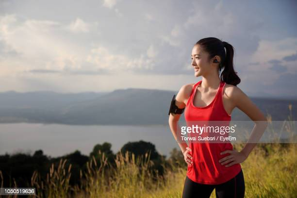 young woman exercising on mountain against cloudy sky during sunset - torwai stock pictures, royalty-free photos & images