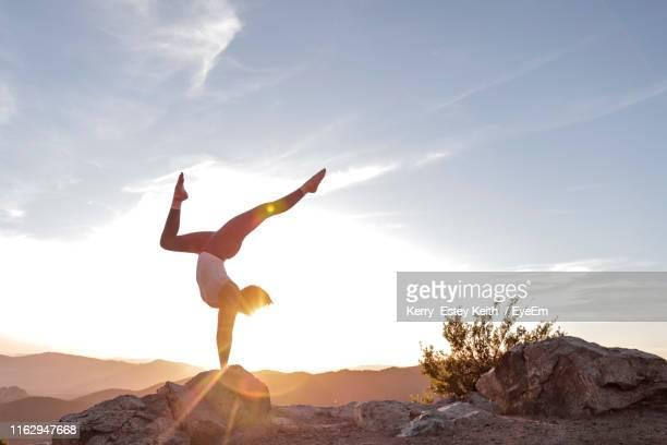 young woman exercising on rock against sky - kerry estey keith stock photos and pictures