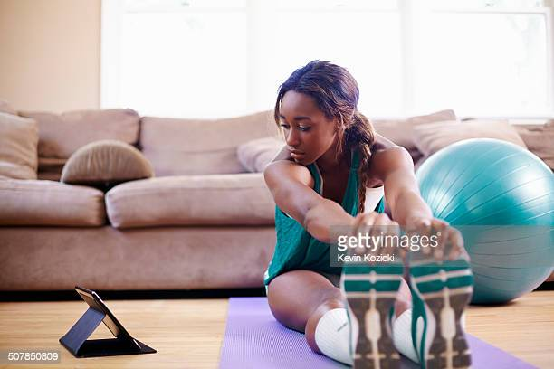 young woman exercising on sitting room floor whilst looking at digital tablet - エクササイズルーム ストックフォトと画像