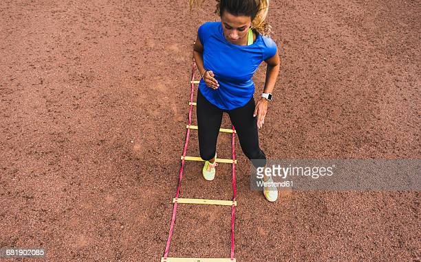 Young woman exercising on sports field with agility ladder